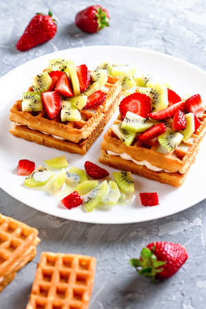 Belgian waffles with fruits strawberries and kiwi on white plate Banque d'images - 124866697