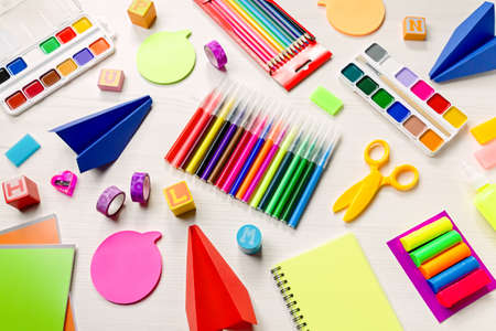School supplies lay out with colorful stationery. Markers, color pencils, notebooks on wooden desk, top view