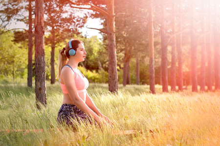 Young attractive slim woman in sport clothes doing yoga, meditating in the park with pine trees in background. Healthy lifestyle concept