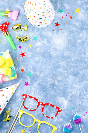 Birthday party accessories and event supplies background with wrapped gifts, confetti, balloons, party hats, decorations, copy space