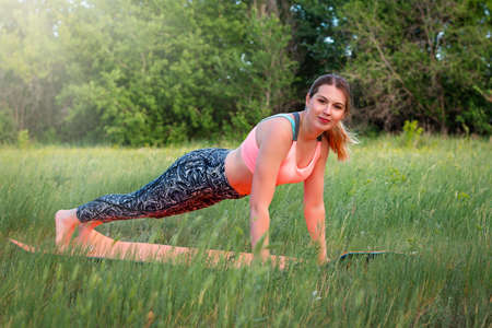 Young attractive slim woman doing plank in the park. Healthy lifestyle concept