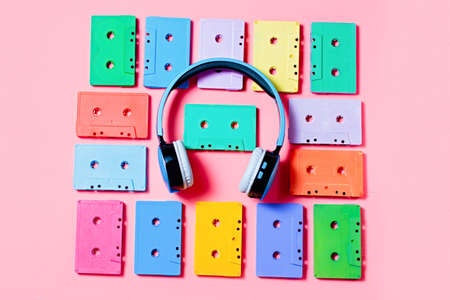 Painted audio cassettes and blue headphones on pink background, copy space, top view. Retro musical background