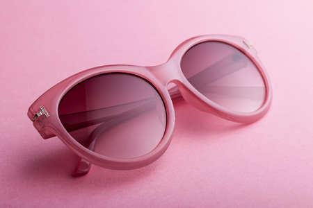 Classic oval oversized pink sunglasses closeup on pink background, top view. Trendy retro shades