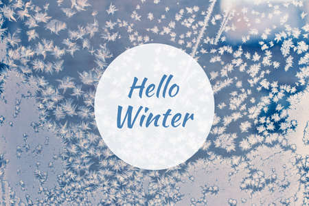 Hello winter greeting card with frosted window and snowflakes