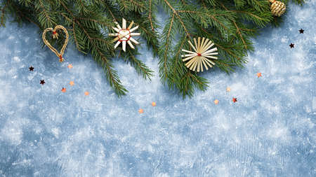 Christmas card with fir tree branches, red ribbons and decorations, wooden ornaments, confetti. Copy space, top view