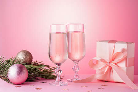 Two glasses of sparkling wine, gift box with bow, decorations. Composition in pink for Christmas, New Year. Still life with drinks and wrapped gift Stock Photo