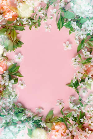 Spring cherry blossom. White cherry flowers frame on pastel pink background. Greeting card with white flowers and bokeh, copy space, top view