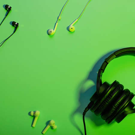 Headphones of different types flat lay on mint color background, copy space. Black headphones closeup with cable, music concept, top view.
