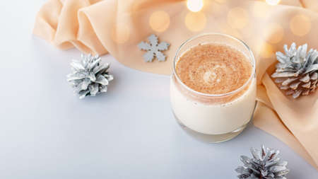 Traditional Christmas cocktail Eggnog with eggs, alcohol, grated nutmeg and cinnamon closeup. Sweet traditional drink for Christmas and winter on table with red decorations and golden pine cones