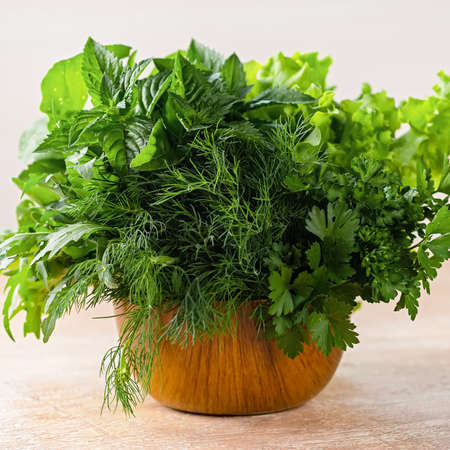 Different fresh herbs in a wooden bowl on a table, copy space Zdjęcie Seryjne