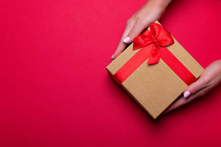 Woman manicured hands holding red and golden wrapped present or giftbox on deep red background, copy space, top view. Flat lay, giving presents concept. Background for Valentines Day, Mothers Day.