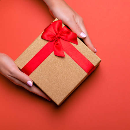 Woman manicured hands holding red and golden wrapped present or giftbox on deep red background, copy space, top view. Flat lay, giving presents concept. Background for Valentine's Day, Mother's Day. Stock Photo