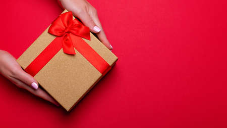 Woman manicured hands holding red and golden wrapped present or giftbox on deep red background, copy space, top view. Flat lay, giving presents concept. Background for Valentine's Day, Mother's Day. Stock Photo - 132115843