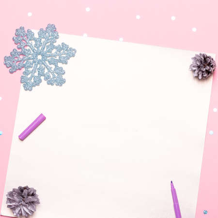 Woman manicured hands holding pen and writing goals and plans for new year. Flat lay on pastel pink desk with confetti and christmas decorations, top view