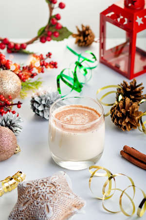 Traditional Christmas cocktail Eggnog with eggs, alcohol, grated nutmeg and cinnamon closeup. Sweet traditional drink on grey table with beige decorations, burning lanterns and pine cones