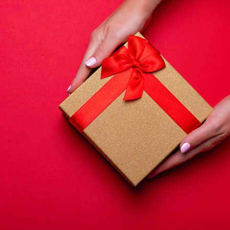Woman manicured hands holding red and golden wrapped present or gift box on deep red background, copy space, top view, flat lay. Background for Valentines Day, Mothers Day.