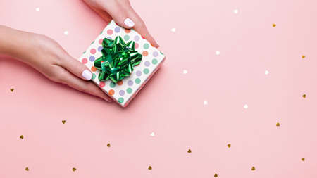 Woman manicured hands holding green giftbox on pastel pink background with confetti, copy space, top view, flat lay. Giving presents or shopping concept. Background for holidays