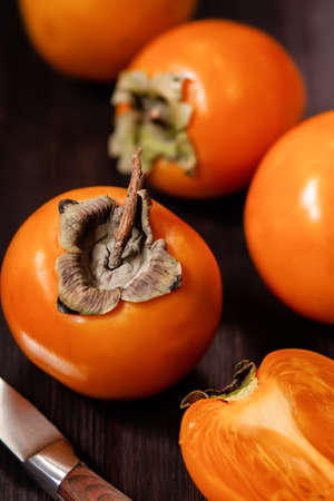 Sweet, ripe persimmon fruit close up on dark background. Food still life with tropical fruit in rustic style, copy space. Healthy eating concept