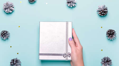 Woman manicured hands holding silver gift box on blue background with pine cones and confetti, copy space, top view, flat lay. Background for Christmas or New Year. Giving presents concept Zdjęcie Seryjne
