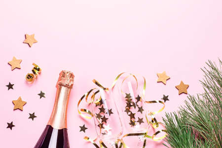 Two champagne glasses with confetti and streamers, golden champagne bottle, green natural fir tree on pastel pink background, copy space. Festive flat lay composition for Christmas or New Year. Zdjęcie Seryjne