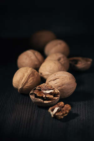 Whole and open walnuts close up on dark wooden background. Food background with walnuts in rustic style, copy space. Healthy eating concept
