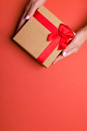 Woman manicured hands holding red and golden wrapped present or gift box on orange brown background, copy space, top view, flat lay. Background for Valentines Day, Mothers Day.