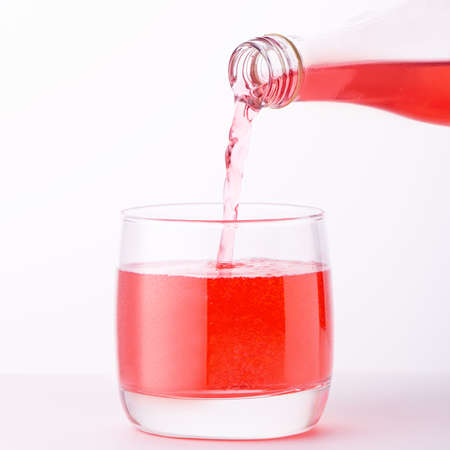 Pouring a refreshing red bubbly soda drink from bottle into glass on white background closeup
