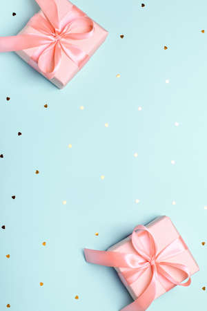 Pink wrapped present or pastel pink gift box with bow on pastel blue background with hearts confetti, copy space, top view, flat lay. Background for Valentines Day, Mothers Day or anniversary