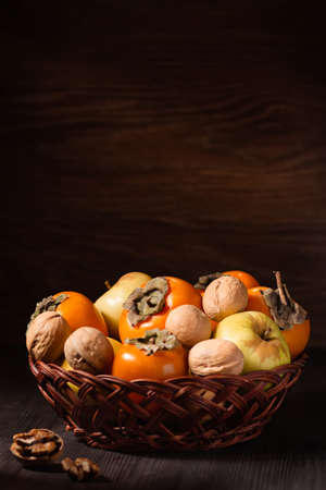 Autumn fruits and nuts in a basket, wooden background. Copy space. Food still life with persimmon, walnuts, apples, rustic style