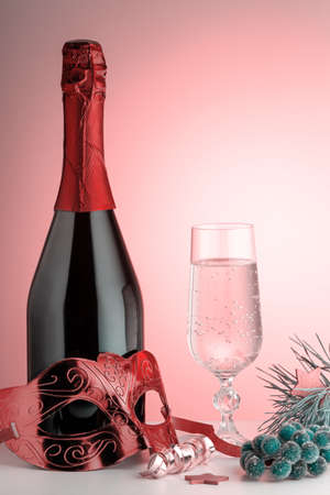 Glass of champagne, bottle, carnival mask and ornaments on pink background. Still life with pink bubly drink, masquerade accessories, copy space