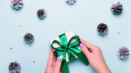 Woman with manicure holding green gift box or wrapped present on blue background with painted silver pine cones and confetti. Christmas presents or shopping concept. Top view 스톡 콘텐츠