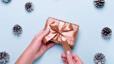 Woman with manicure holding craft paper gift box or wrapped present on blue background with painted silver pine cones and confetti. Christmas presents or shopping concept. Top view Zdjęcie Seryjne