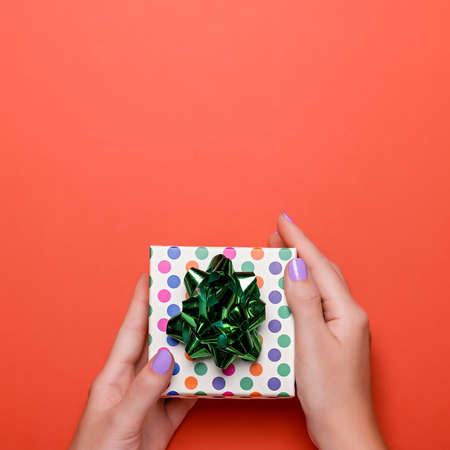 Woman manicured hands holding green giftbox on orange background with confetti, copy space, top view, flat lay. Giving presents or shopping concept 스톡 콘텐츠