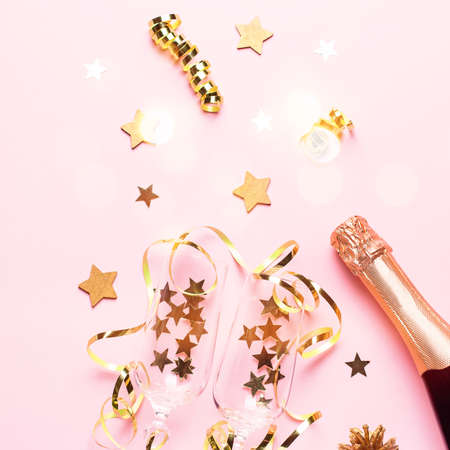 Two champagne glasses with confetti and streamers, golden champagne bottle, green natural fir tree on pastel pink background, copy space. Festive flat lay composition for Christmas, New Year. Zdjęcie Seryjne