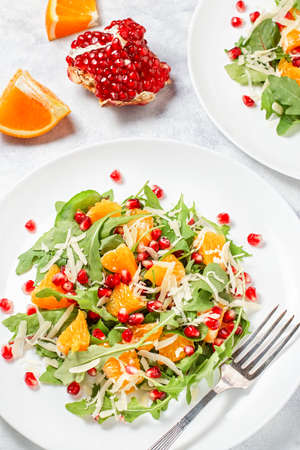 Fresh green organic salad with raw ingredients close up. Tasty salad with arugula, orange slices, pomegranate and cheese on white plate, top view. Healthy eating, dieting concept, raw food