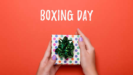 Woman manicured hands holding green giftbox on orange background with confetti, copy space, top view, flat lay. Giving presents or shopping concept Zdjęcie Seryjne