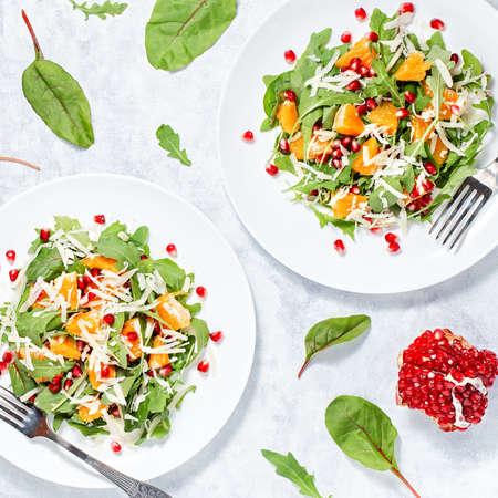 Verse groene biologische salade met rauwe ingrediënten close-up. Lekkere salade met rucola, stukjes sinaasappel, granaatappel en kaas op witte plaat, bovenaanzicht. Gezond eten, dieetconcept, raw food