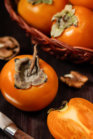 Sweet, ripe persimmon fruit in paper close up on dark background. Food still life with tropical fruit in rustic style. Healthy eating concept