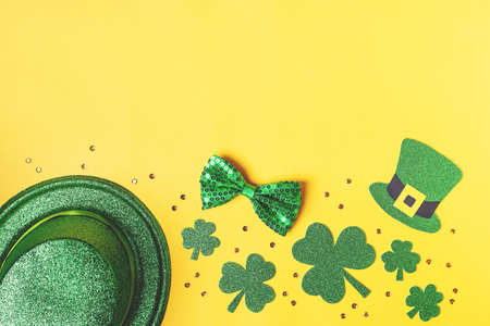 Saint Patrick's day holiday card with green shamrock symbols, hat, golden confetti. Traditional St. Patrick's Day green attire and decorations on yellow background. Web banner, copy space, top view