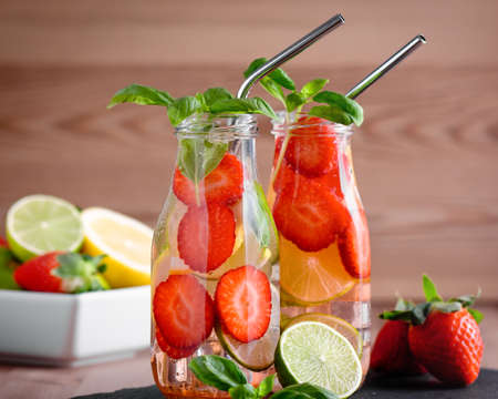 Refreshing drink or water with citrus fruits lemon and lime and basil in mason jar with reusable metal straws. Healthy lemonade drink in glass jar on kitchen table, zero waste, sustainable lifestyle 스톡 콘텐츠 - 141655542