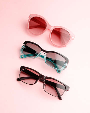 Collection of fashionable sunglasses on pink background. Sunglasses of different shapes and colors flat lay. Oval shaped sunglasses, oversized, wayfarer frames.