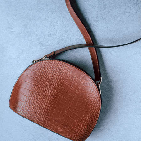 Woman handbag or purse reptile leather style in brown color closeup, top view. Minimal fashion background with saddle type cross body bag on grey concrete