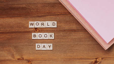 Words world book day made of wooden blocks with black eyeglasses and stack of books. Background for book holiday on wooden table top 写真素材