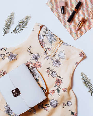 Fashion female clothes and accessories for beach destinations or summer vacation. Flat lay with woman white clothing and purse, make up items on terracota background, woman travel fashion concept Standard-Bild - 143155919