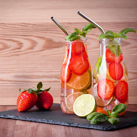 Refreshing drink or water with citrus fruits lemon and lime and basil in mason jar with reusable metal straws. Healthy lemonade drink in glass jar on kitchen table, zero waste, sustainable lifestyle Foto de archivo