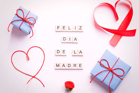 Happy Mother's Day greeting card with red hearts, blue gift boxes and golden confetti on pastel table top, overhead shot. Feliz dia de la madre text from wooden blocks that mean Happy Mothers day