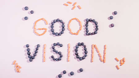 Vitamins and supplements for healthy eyes on pink background. How to maintain good vision concept. Blueberry and orange capsules forming words good vision