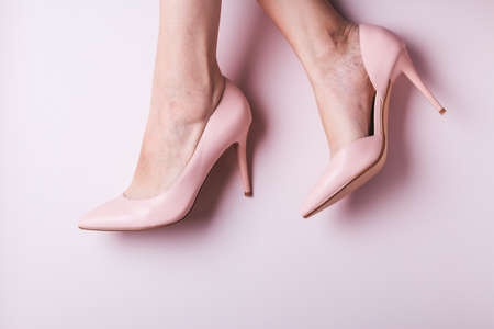 Woman feet in pink shoes closeup with small spider veins, leg disease. Unhealthy side effect of wearing high heels that provokes varicose veins, copy space, top view