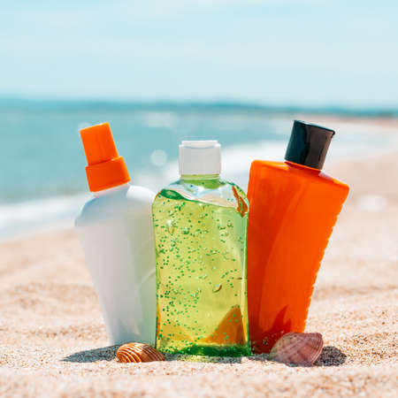 Bottles of sun protection lotion, aloe soothing gel from sun burn, seashells in sand on the beach with sparkling sea in backaground. Close up of sun protection cosmtic products, copy space Stok Fotoğraf