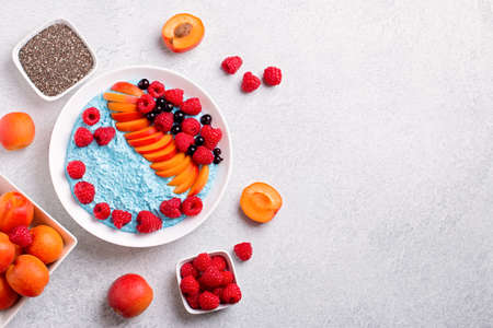 Chia seeds pudding bowl with apricot, raspberry on concrete background. Blue mousse with chia seeds, berries and fruits for healthy breakfast, top view